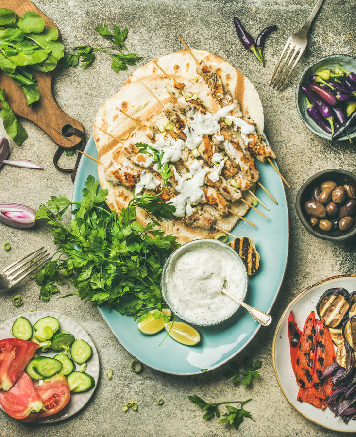 Summer barbecue party dinner set with grilled chiken and vegetables. Summer barbecue party dinner set. Flatlay of grilled chicken skewers with yogurt dip royalty free stock images