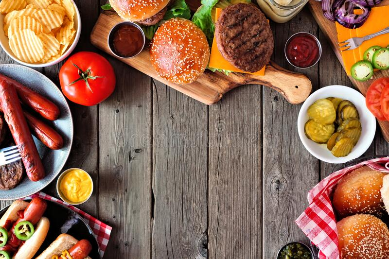 Summer BBQ food frame with hot dog and hamburger buffet, above view over a dark wood background stock photography