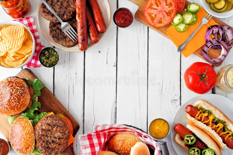 Summer BBQ food frame with hot dog and hamburger buffet, overhead against a white wood background stock photo