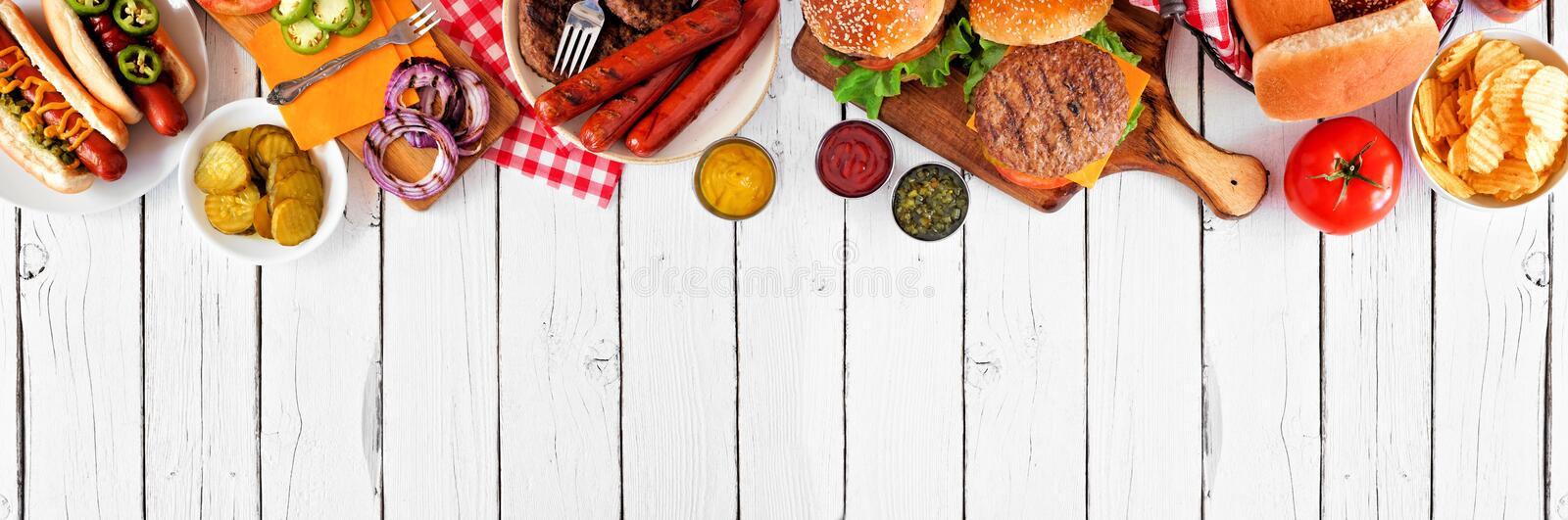 Summer BBQ food with hot dog and hamburger buffet, top border over a white wood banner background stock images