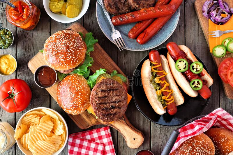 Summer BBQ food table scene with hot dog and hamburger buffet, top view over dark wood stock photography