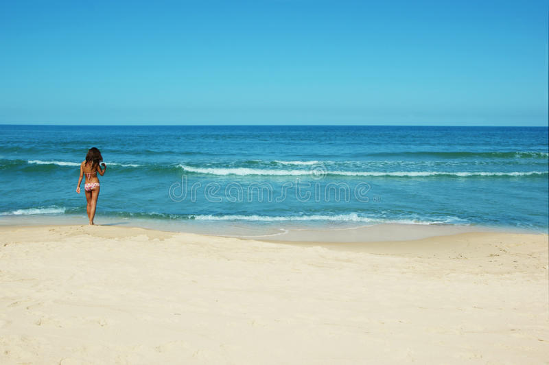 Summer on the beach. Beautiful slim girl going sea bathing on a sunny summer day royalty free stock photo