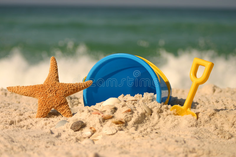 Summer at the Beach. A summer beach scene with a starfish and beach toys set against the ocean surf. Shot with shallow DOF royalty free stock photos