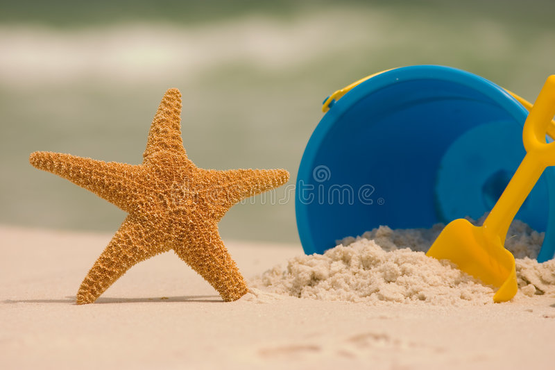 Summer at the Beach. A summer beach scene with a starfish and beach toys set against the ocean surf. Shot with shallow DOF royalty free stock images