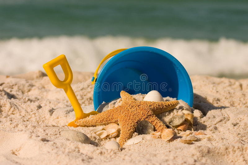 Summer at the Beach. A summer beach scene with a starfish, sea shells, and beach toys set against the crashing ocean surf. Shot with shallow DOF royalty free stock photo