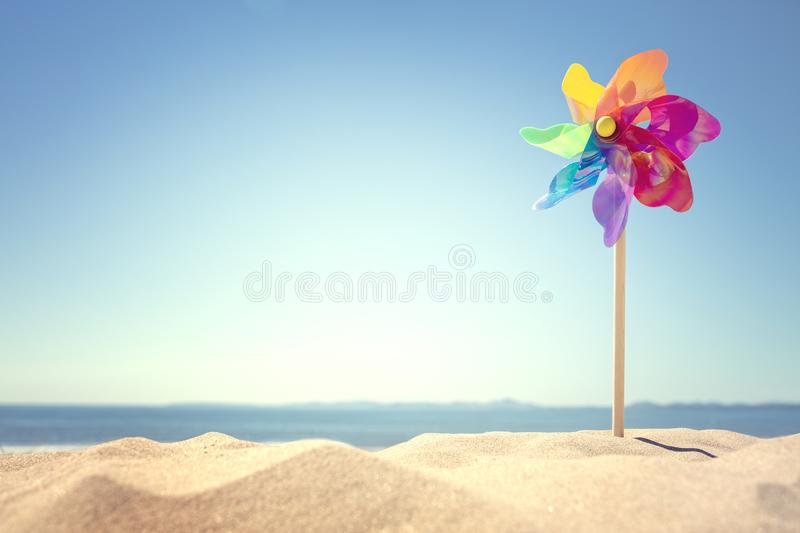 Summer beach background. Pinwheel or windmill in the sand concept for vacation copy or message royalty free stock photography