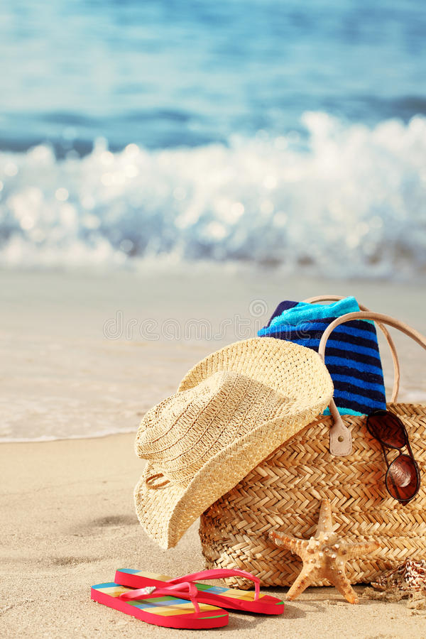 Summer beach bag on sandy beach. Closeup of summer beach bag with items on sandy beach