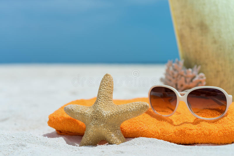 Summer beach bag with towel, sunglasses and coral on sandy beach stock photos