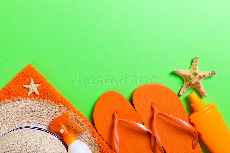 Summer beach flat lay accessories. Sunscreen bottle cream, straw hat, flip flops, towel and seashells on colored Background. stock photography