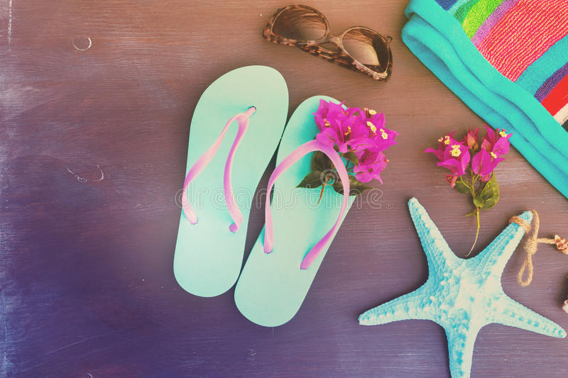 Summer beach fun. Sandals with sunglasses, flowers and starfish, retro toned stock image