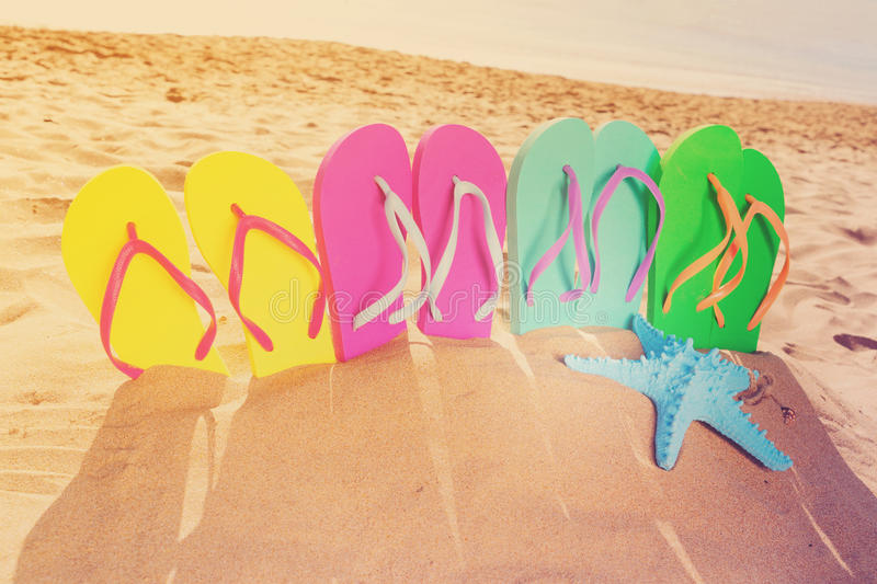 Summer beach fun. Set of colorful family sandals - green, blue, pink and yellow - in sand, retro toned royalty free stock photos