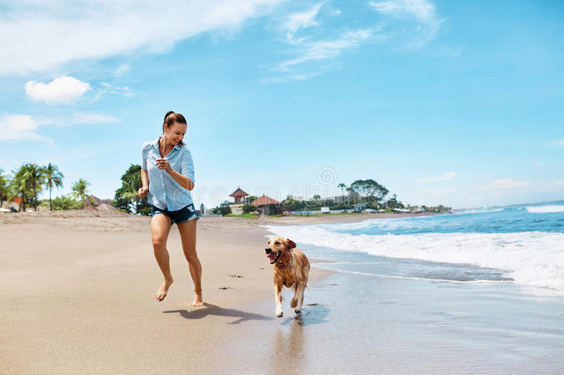 Summer Beach Fun. Woman Running With Dog. Holidays Vacations. Summer. Summer Fun On Beach. Beautiful Happy Woman Running With Her Dog, Golden Retriever, Pet On royalty free stock photo