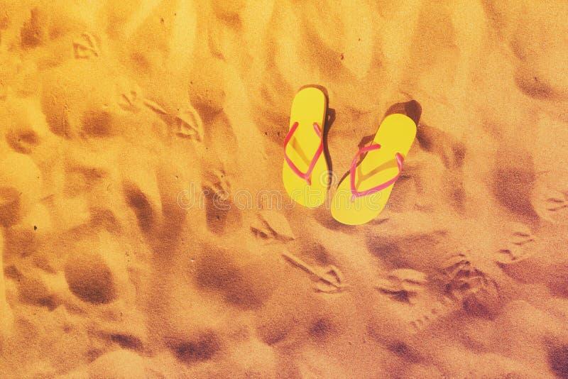 Summer beach fun. Yellow flip-flops with seagull footprints on beach sand, retro toned stock photo