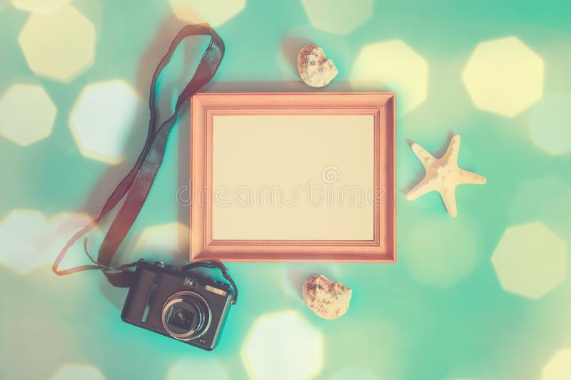 Summer beach holiday concept. Photo frame, photo camera, starfish and seashells on blue background stock photo