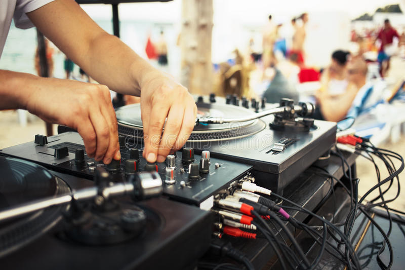 Summer beach party with music. Hands of DJ spinning record albums outside at summer beach party royalty free stock photos