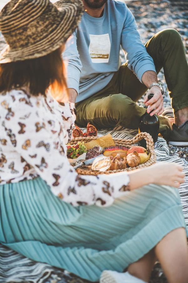 Young couple having picnic with sparkling wine, fruit and snacks stock photos