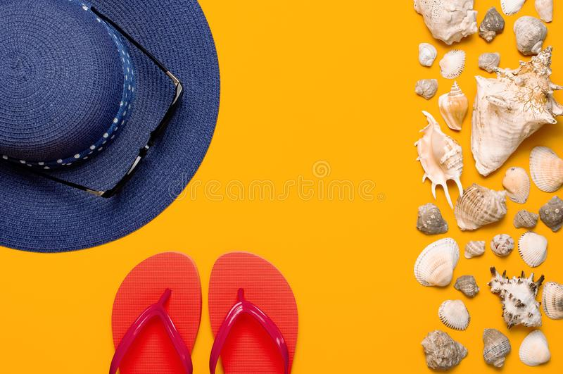 Summer beach sea accessories. Coral flip flops, blue straw hat, sunglasses, shells, starfish on yellow background top view flat royalty free stock photos
