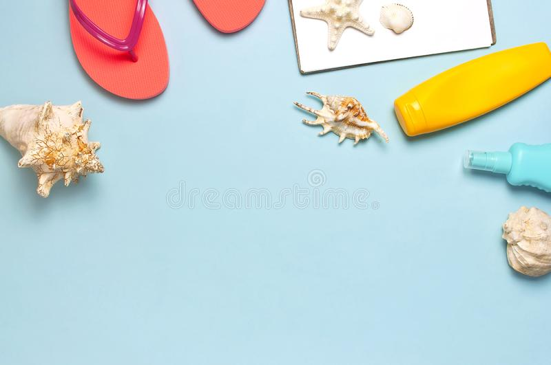 Summer beach sea accessories. Coral flip flops, shells, starfish, yellow sunscreen bottle, body spray on blue background top view stock photo