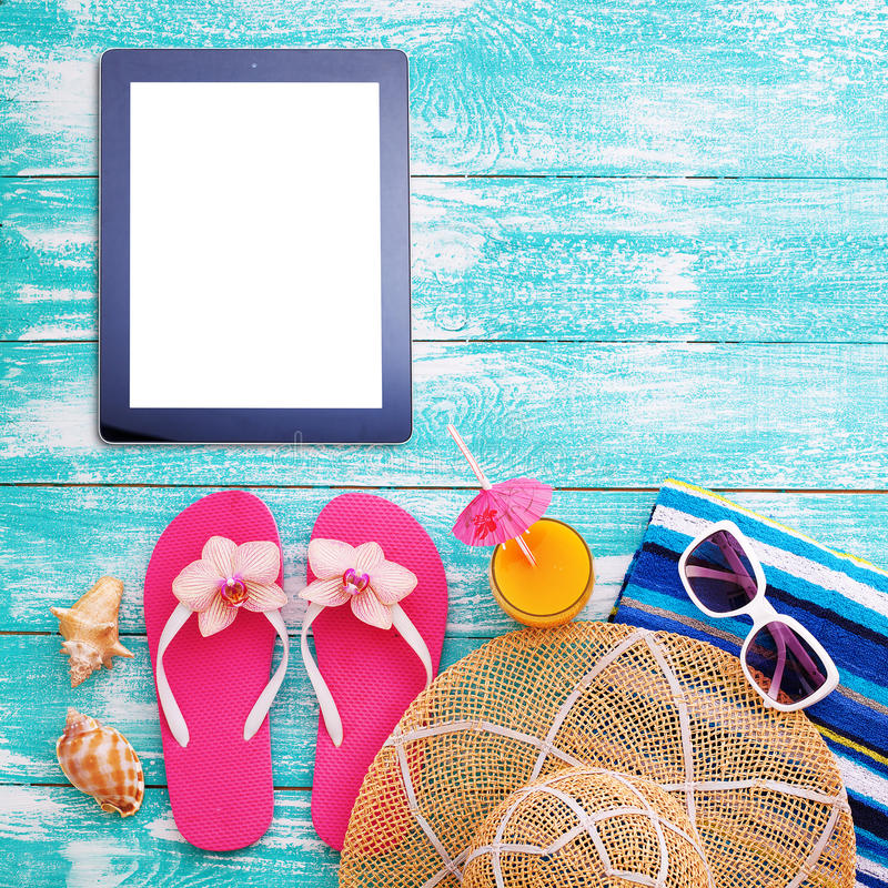 Summer beach, set of summer accessories and tablet. Workplace for freelancer royalty free stock photography
