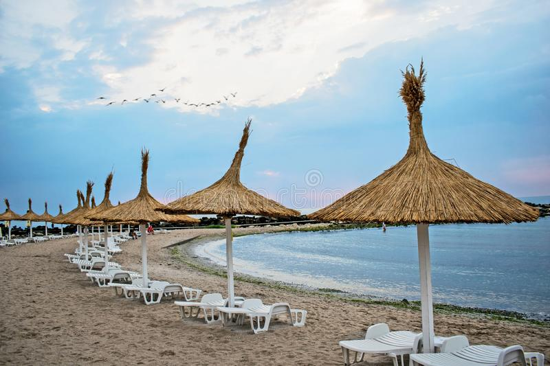 Summer, on the beach, sunbeds and umbrellas, before a storm begins.  stock image