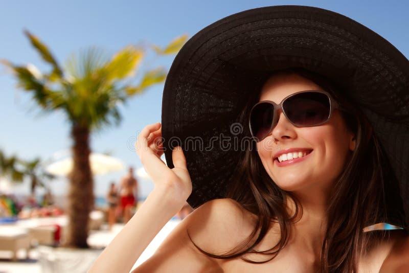 Summer beach teen girl cheerful in panama and sunglasses. Enjoying royalty free stock photo