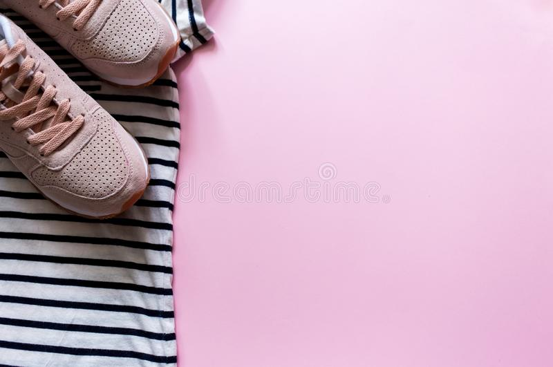 Summer beach travel clothes and pink leather sneakers. Flatlay of a trendy woman fashion outfit. Sport clothes. stock photography