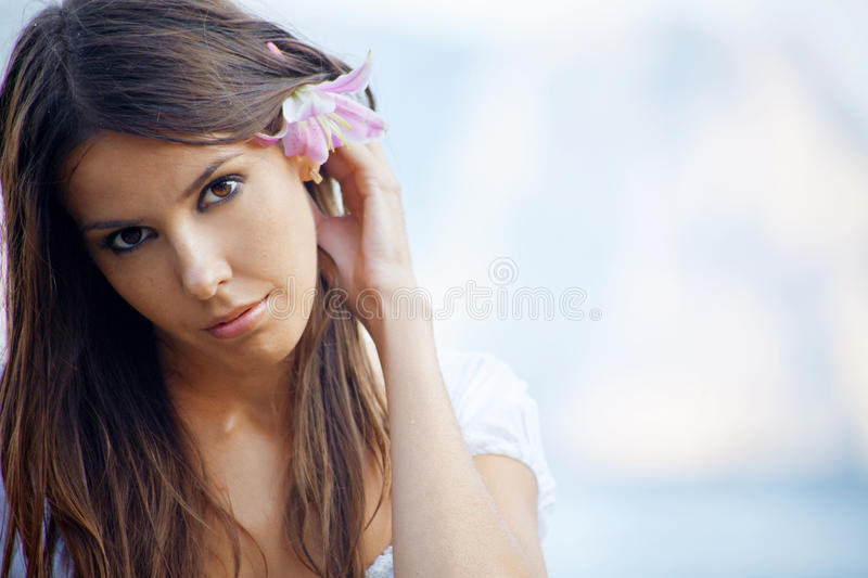 Summer beautiful female with flower in her hair. Closeup portrait of beautiful brunette woman with lily in her hair posing over sea royalty free stock photo
