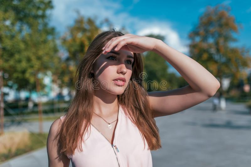 In summer, a beautiful girl in the city looks into distance, covers her eyes with her hand from bright sun. Long hair. In summer, a beautiful girl in the city royalty free stock photography