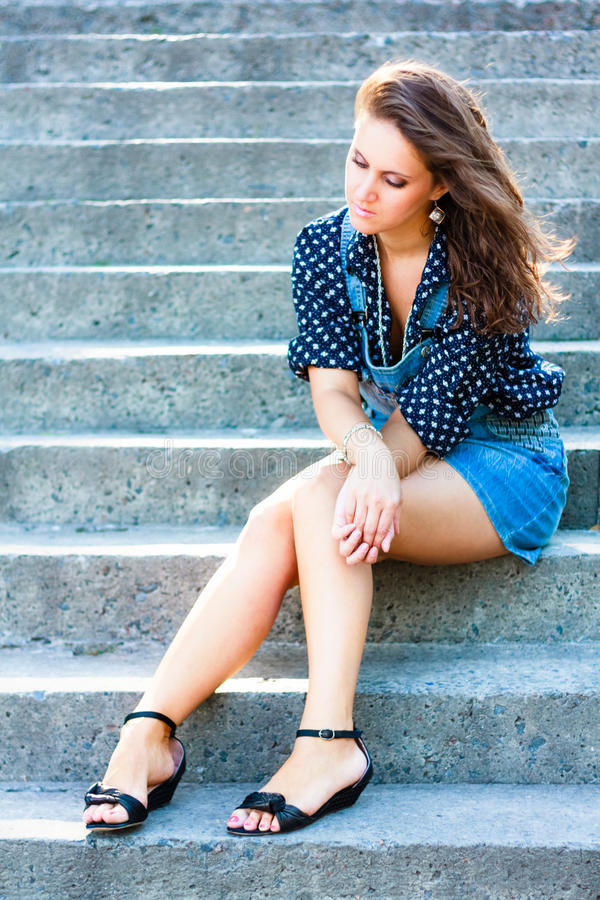 Summer beautiful girl portrait. Pretty young caucasian depressed woman sitting on staircase stock photo