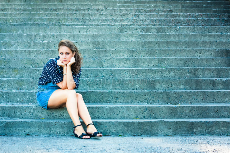 Summer beautiful girl portrait. Pretty young caucasian depressed woman sitting on staircase royalty free stock images