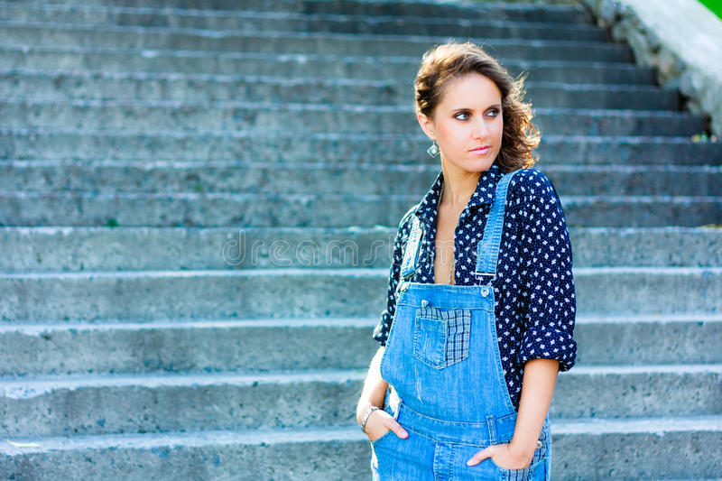 Summer beautiful girl portrait. Pretty young caucasian happy woman standing on staircase royalty free stock photo