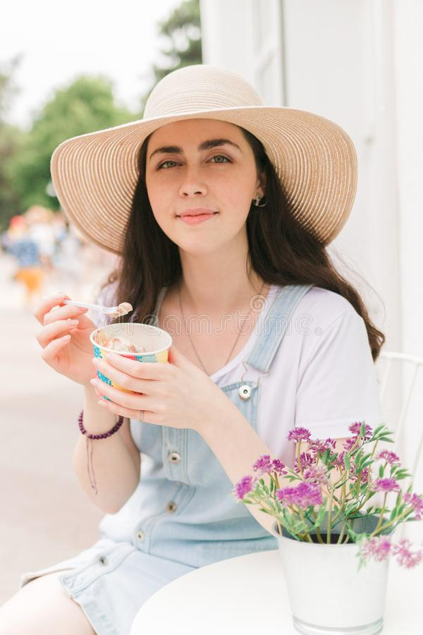 Summer. Beautiful young woman sitting in a cafe and eating ice cream. Close up royalty free stock images