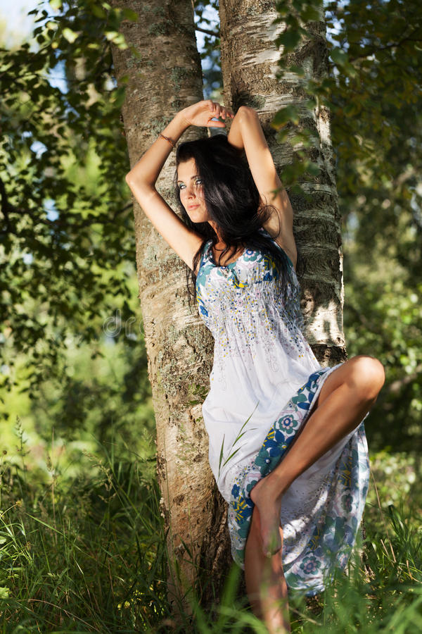 Summer beauty. Girl in summer dress behind the birch stock images