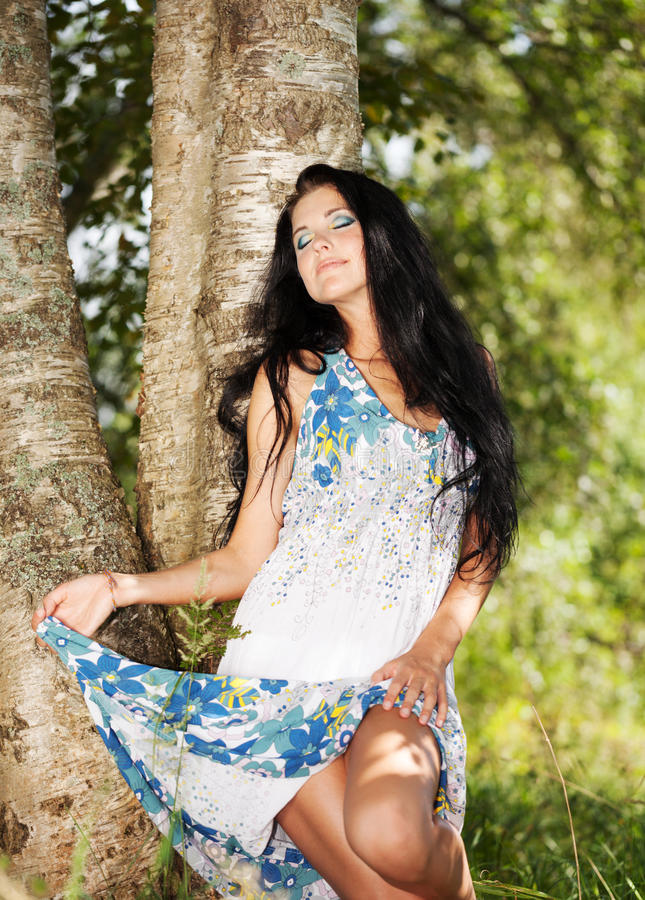 Summer beauty. Girls in sundress inder the birch with eyes closed stock photos