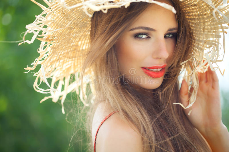 Summer Beauty. Young woman in straw hat smiling in summer outdoors stock photos