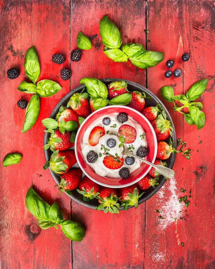 Summer berries blackberries, blueberries, strawberries with cottage cheese, basil leaves and spoon on red wooden background stock images