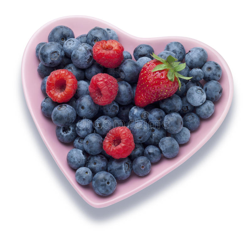 Summer Berries Heart Food. A heart shaped plate full of summer berries on a white background demonstrating a healthy diet