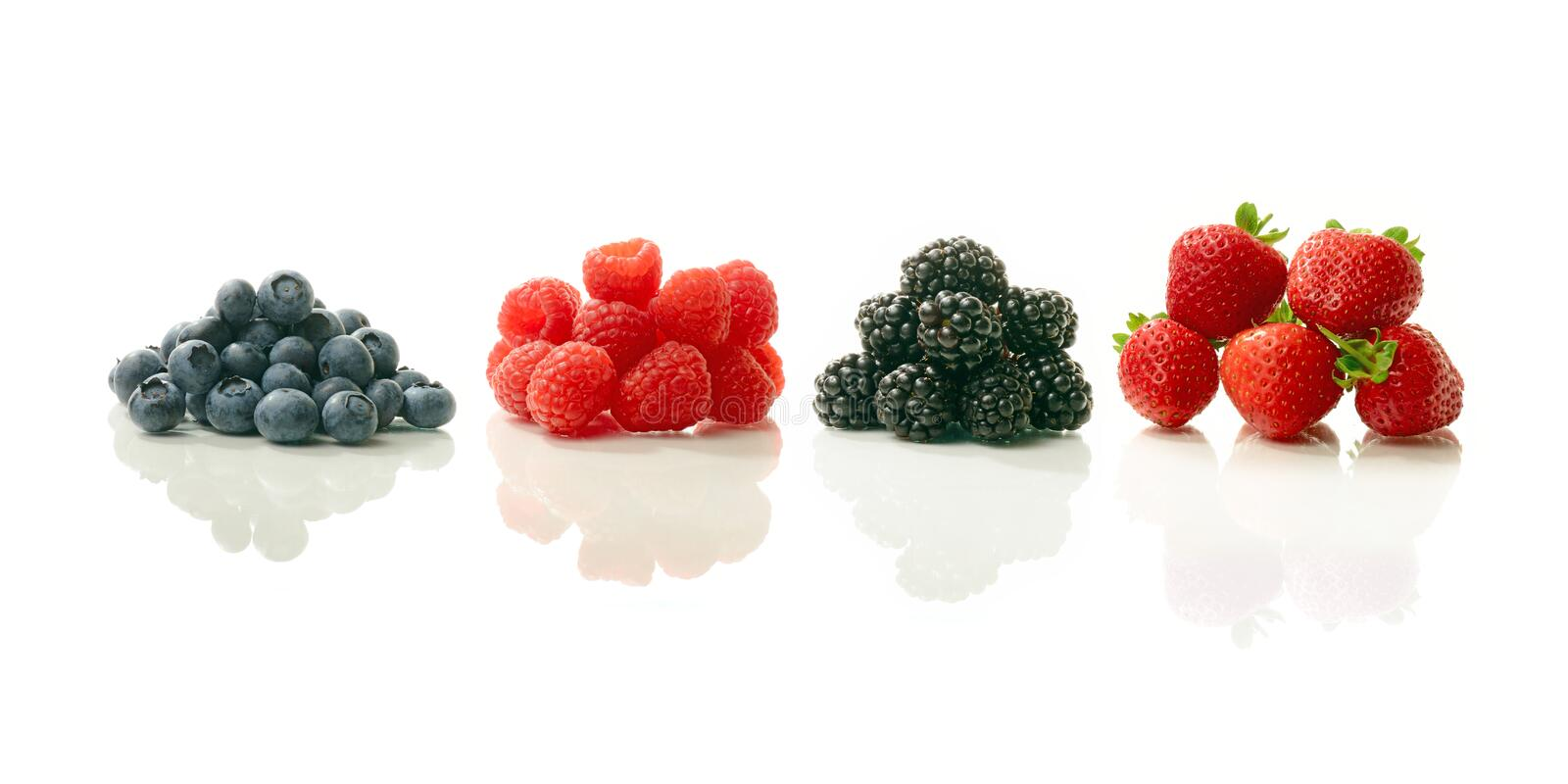 Summer Berries. A studio image of fresh, ripe summer berries. Blueberries, raspberries, blackberries and strawberries all with soft reflections against a white stock photography