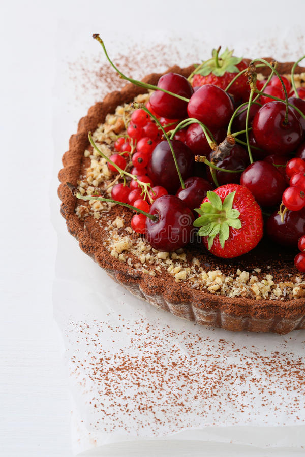 Summer berry tart on white wood background. Food closeup stock image