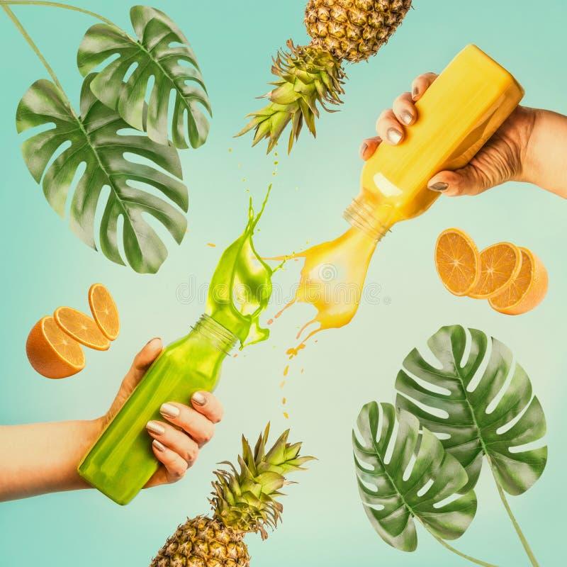 Summer beverages concept. Female hands holding bottles with splash smoothie or juice on blue background stock image
