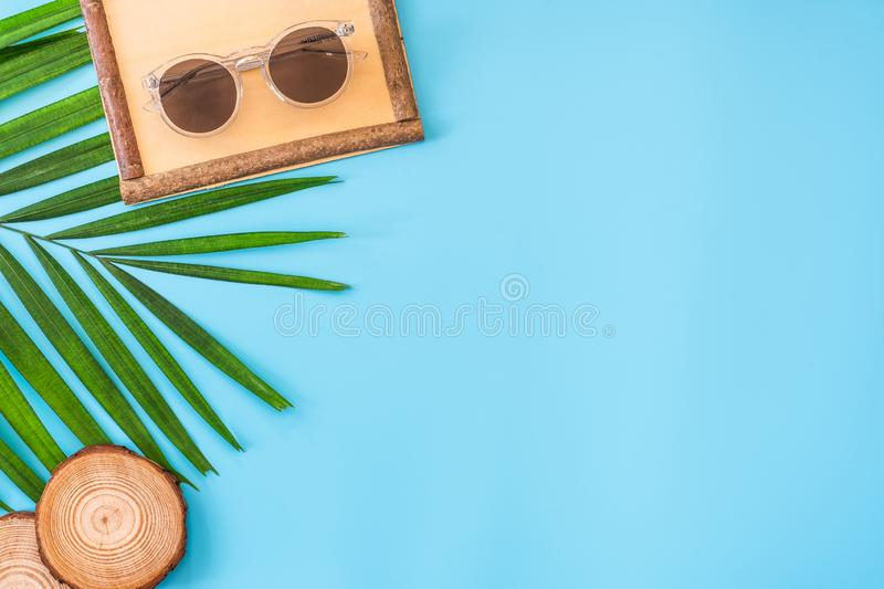 Summer blue banner with wood picture grame ,sunglasses,seashell and palm leaf on blue background top view royalty free stock images
