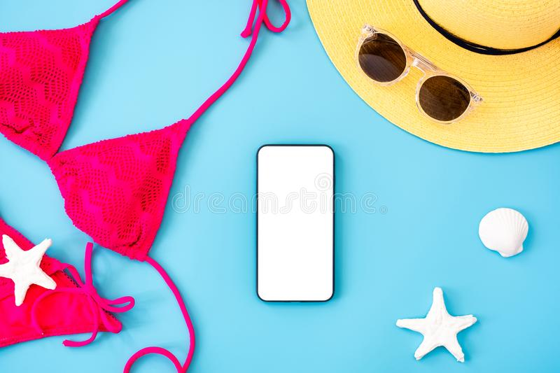 Summer blue banner with yellow hat ,pink bikini,mobile ,sunglasses and seashell on blue background top view mock up screen royalty free stock images