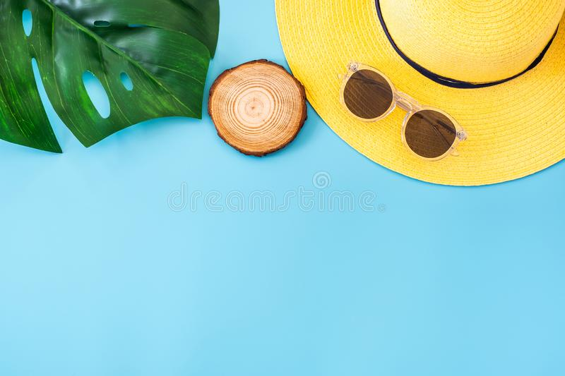 Summer blue banner with yellow hat ,sunglasses and monstera leaf on blue background top view royalty free stock photos