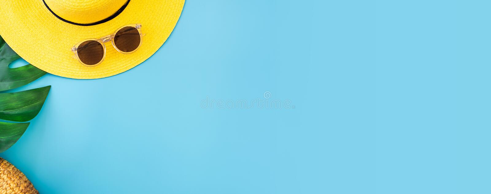 Summer blue banner with yellow hat ,sunglasses and monstera leaf on blue background top view royalty free stock photo