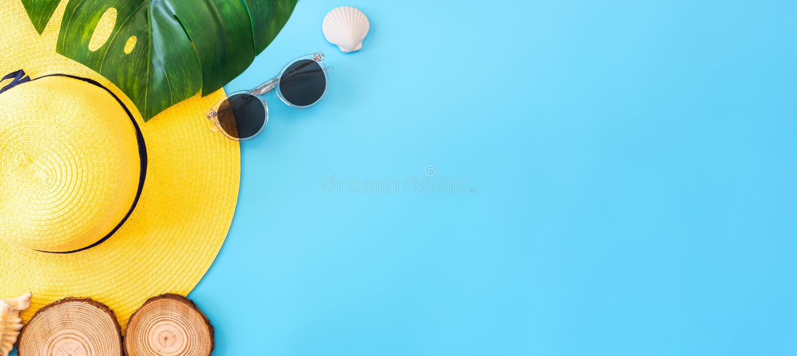 Summer blue banner with yellow hat ,sunglasses,seashell and monstera leaf on blue background top view royalty free stock image
