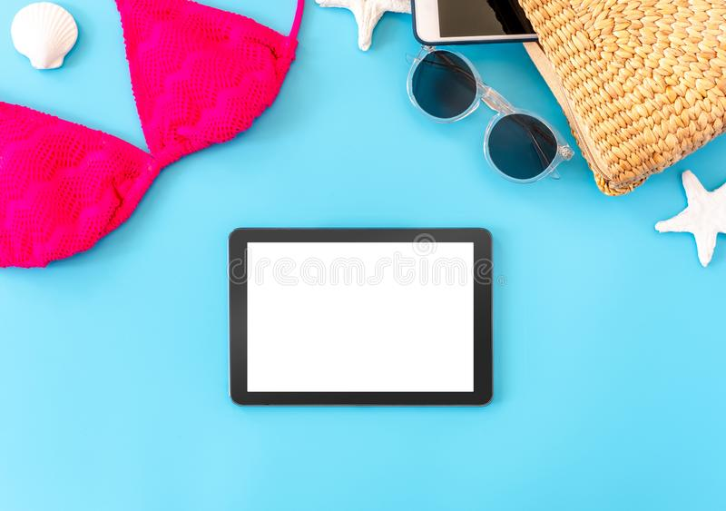 Summer blue banner with yellow wicker bag ,pink bikini,tablet ,sunglasses and seashell on blue background top view mock up screen royalty free stock photography