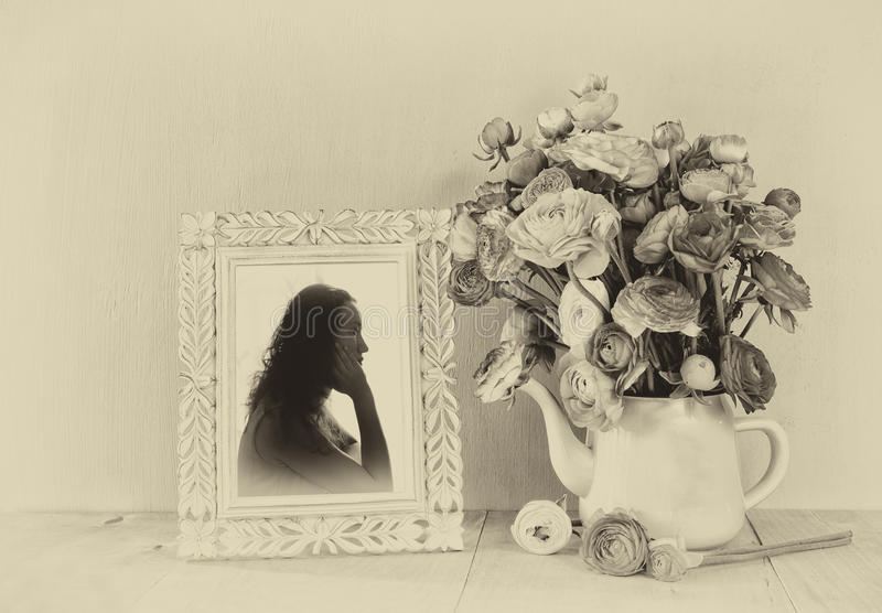 Summer bouquet of flowers and victorian frame with vintage portrait of young woman on the wooden table. black and white style. Image with textured overlay stock images