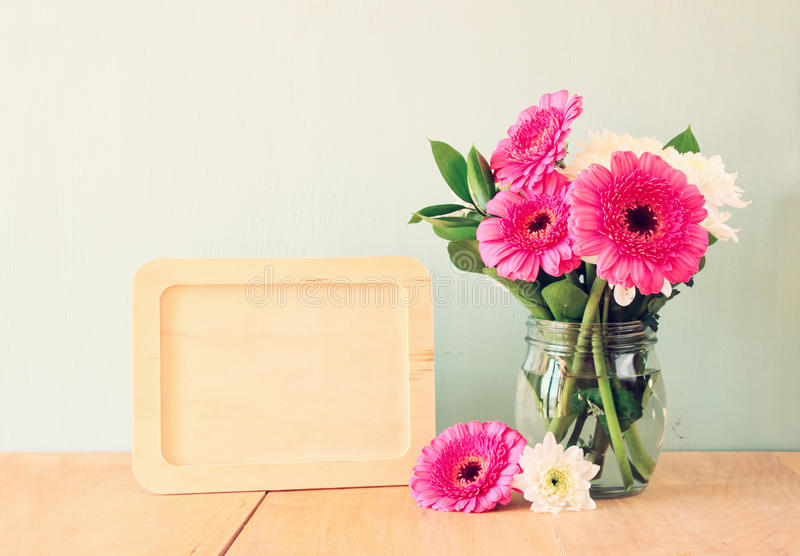 Summer bouquet of flowers on the wooden table and wooden board with room for text with mint background. vintage filtered image royalty free stock photography