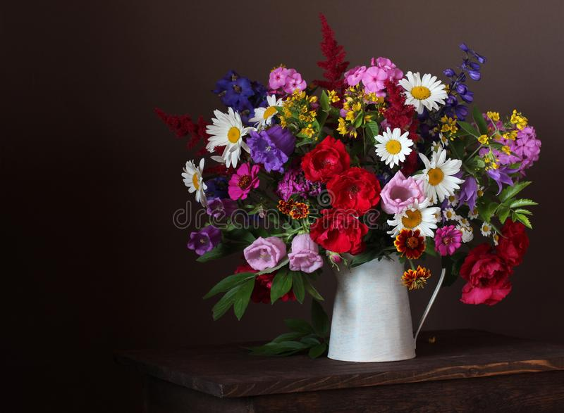 Summer bouquet in a jar: roses, daisies, Phlox, bells and other garden flowers. On a dark background royalty free stock photo