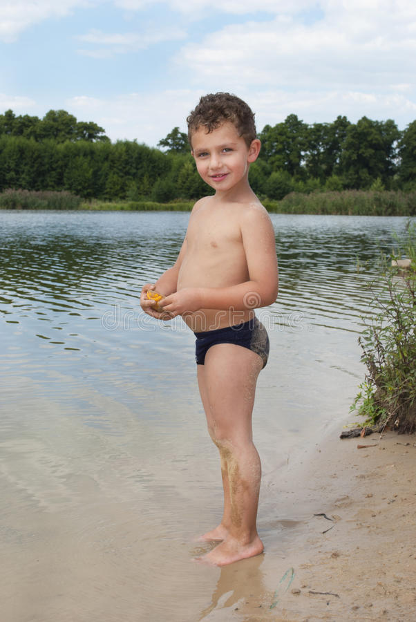 Free Summer Boy Stands On The Sand Near The Lake. Royalty Free Stock Photo - 37757885